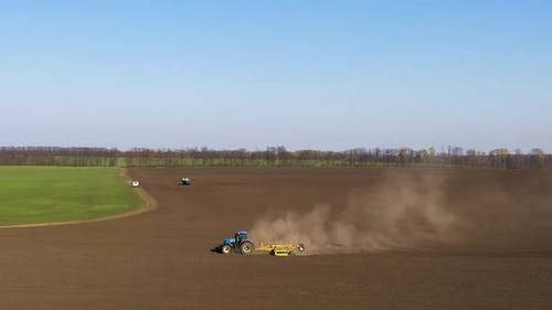 The Stubble-Tillage Cultivation After Harvest With Big Blue Modern Tractor Aggregated With Equipment