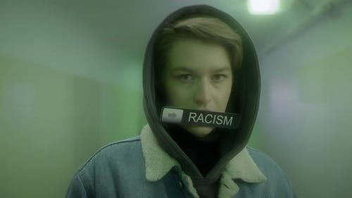 Woman in a Hood and Denim Jacket Holds a Sign with Inscription  STOP RACISM