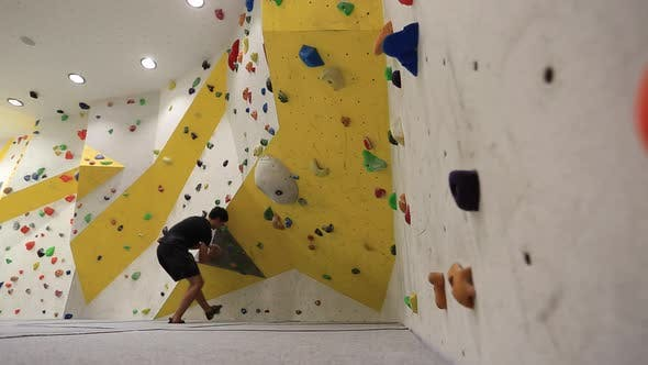 Thumbnail for Wide shot of a young man who climbs in an indoor climbing gym.