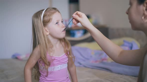 Thumbnail for Mother Gives Cough Syrup To Little Girl in Pink Shirt on Bed