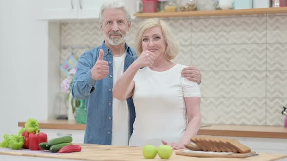 Loving Old Couple Making Heart Shape By Hands While in Kitchen