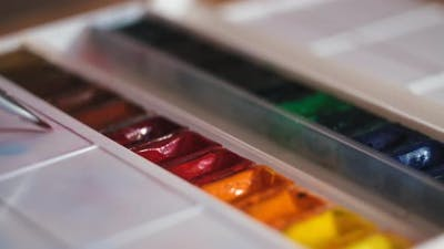 Putting paint brush into colorful oil paints