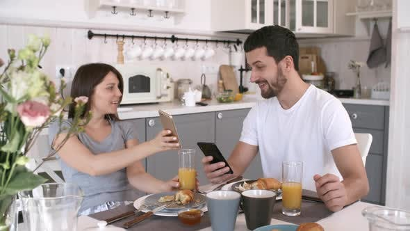 Thumbnail for Couple with Mobile Phones Eating Breakfast
