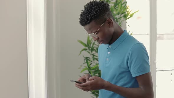 Thumbnail for Thoughtful African American Student in Eyeglasses Using Smartphone.