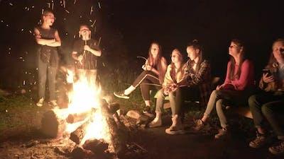 Teens Looking at Bright Campfire.