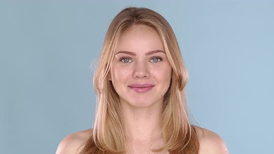 Thumbnail for Potrait of Beautiful Blond Woman with Long Hair, Posing in Studio on Blue Background