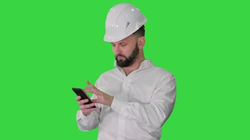 Smart Engineer in White Shirt and Safety Engineering Hat Using Smartphone on a Green Screen, Chroma