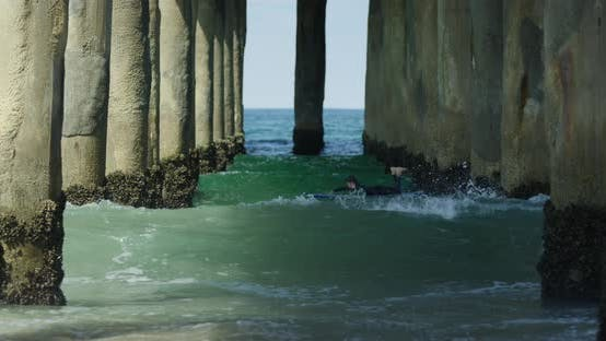 Thumbnail for Surfing under a pier while waves splash and crash
