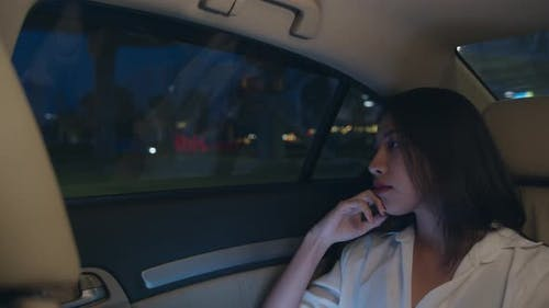 young Asia businesswoman looking out of window car while sit on passenger back seat in urban city.