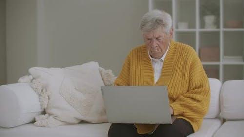 Eine ältere Frau, die auf der Couch sitzt, druckt eine Nachricht auf der Tastatur