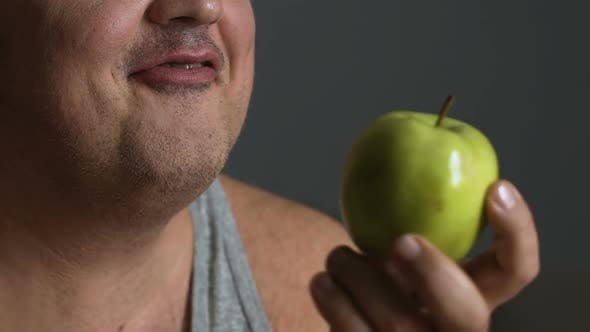 Cover Image for Overweight Man Biting Fresh Apple, Keeping to A Healthy Diet to Lose Weight