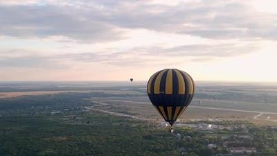 Dolly Zoom Shot of Colorful Hot Air Balloon Flying Over Countryside Near Small European City at