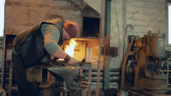 Blacksmith Processes the Product on the Anvil