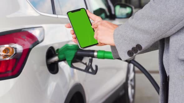 Woman Uses a Mobile Application in a Smartphone To Pay for Refueling a Car. Smartphone with a Green