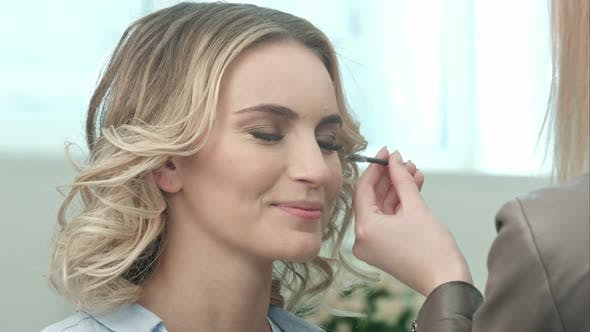Thumbnail for Professional Make-up Artist Combing Eyelashes of Model in White Room
