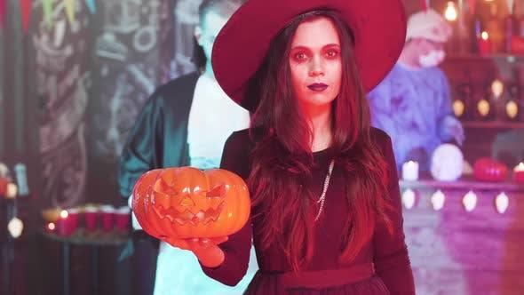 Junge schöne Frau in schwarz Hexe Kostüm auf einer Halloween-Party