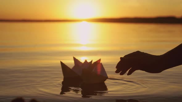 Thumbnail for Human Hand is Launching Handmade Paper Boats Into the Lake at Sunset