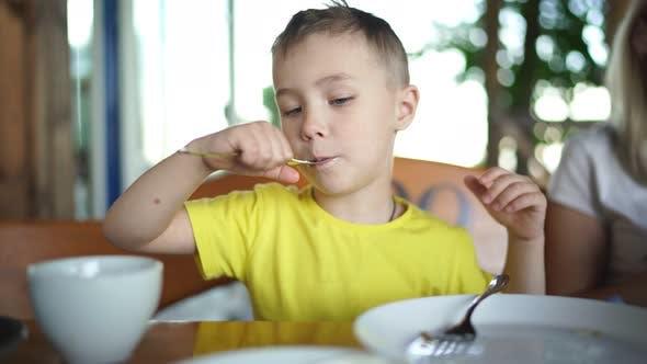Kleiner Junge isst morgens einen Pfannkuchen mit Sauerrahm in einem Café zum Frühstück