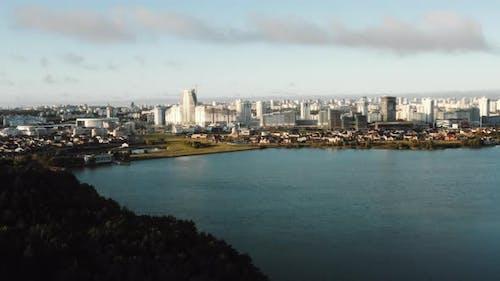 Beautiful Aerial Panorama of Calm Autumn Lake, Modern Futuristic City Skyline Scenery and Forest