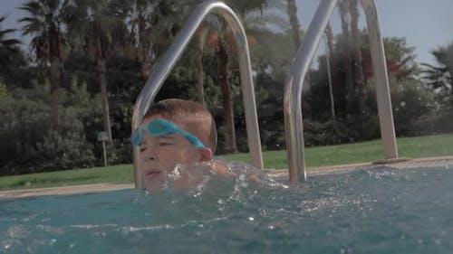 Child having fun in swimming pool and splashing water