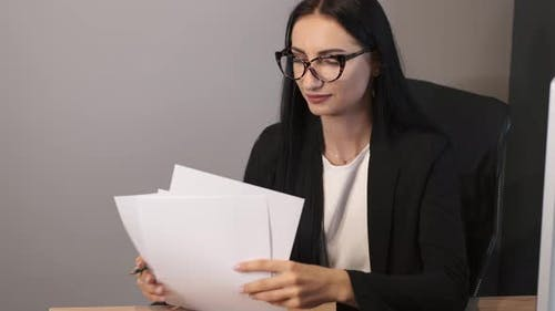 Brunetter Business Woman Working at the Office with Papers