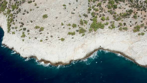 Thumbnail for Drone Flying Over Rocky Coast Line with Deep Blue Sea Water