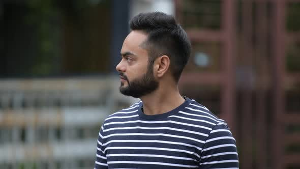 Profile View of Young Bearded Indian Man Waiting and Thinking Outdoors