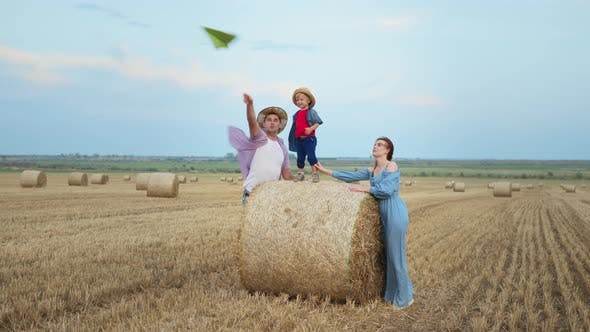 Happy Family with Male Child Standing on a Haystack Launch Paper Plane and Clap Their Hands