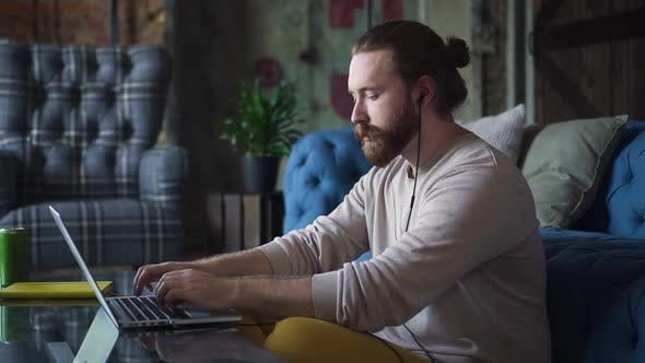 Man at Home Typing on Laptop Listening to Music in Headphones