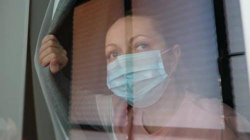 COVID-19 Pandemic Lockdown. Sad Woman on Quarantine in Medical Mask Looking Through Window