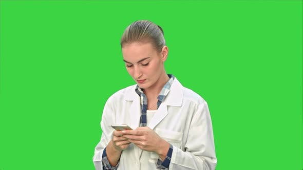 Thumbnail for Female Doctor Using Texting Messages Using Modern Smartphone and Smiling on a Green Screen