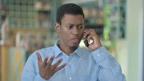 Angry Young African Man Arguing on Smartphone