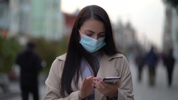 Portrait Woman in Protective Medical Mask Walks Down To the Street Uses Phone Texts Scrolls Surfs