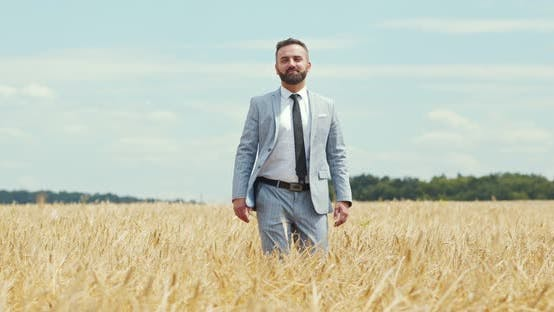 Thumbnail for Confident Caucasian Businessman Walking Through Wheat Field and Smiling, Slow Motion