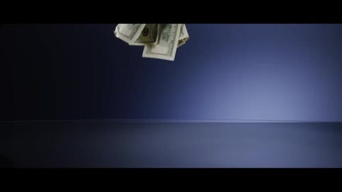American $100 Bills Falling onto a Reflective Surface - MONEY 0009