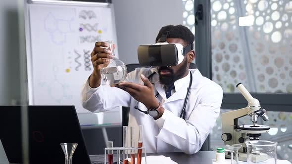 Thumbnail for African American Male Doctor Looking at the Flask with Chemical Liquid Using Virtual Reality Headset