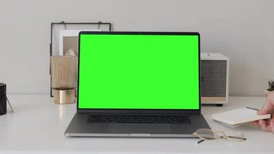 Mock-up Green Screen Laptop macbook pro Standing on the Desk in the Modern Creative Office.