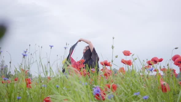 Thumbnail for Pretty Girl Dancing in a Poppy Field Holding Flag of Germany in Hands Outdoors. Connection with