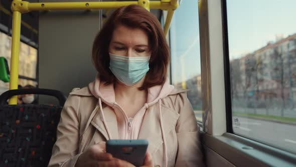 Woman traveling in bus and using phone