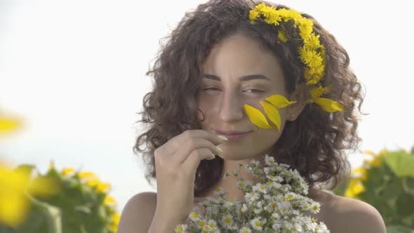 Cover Image for Portrait of a Lovely Curly Girl Looking at the Camera Smiling Standing on the Sunflower Field