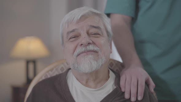 Thumbnail for Close-up Face of Happy Old Man Looking at Camera. Unrecognizable Male Nurse