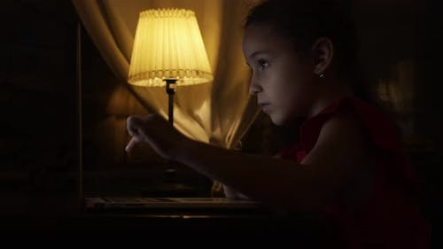 School Child, a Girl of 7-8 Years Old, Studies at Home Remotely in the Evening, Listens To School