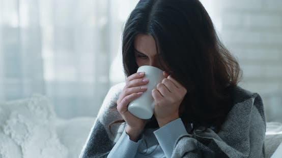 Junge Depressive Frau, Die Hände der Tasse wärmt, Heißen Tee genießt, allein auf dem Sofa sitzend in Plaid