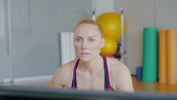 Sportive kaukasische Frau sitzen und erklären Übung. Porträt der Selbstbewussten Sportlerin