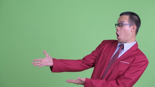 Thumbnail for Happy Asian Businessman with Eyeglasses Showing Something and Looking Surprised