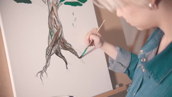 Thumbnail for A Young Woman with Short Hair Painting Tree Trunk in Darker Color