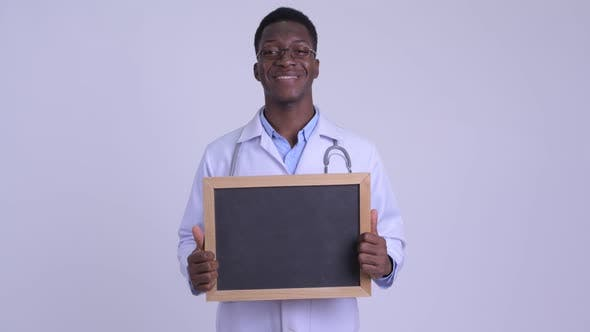 Thumbnail for Young Happy African Man Doctor Holding Blackboard