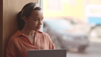 Businesswoman Working on Laptop on Windowsill