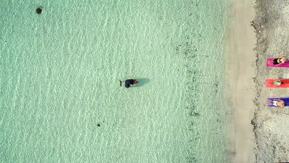Thumbnail for Aerial view of photographer in sea near sandy beach in summer.