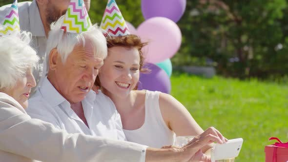 Thumbnail for Grandmother Taking Family Selfie with Smartphone on Outdoor Party